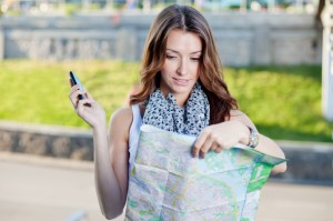 young woman tourist holding paper map outdoors and talking by th